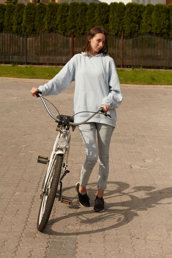 Full length of woman with bicycle standing outdoors