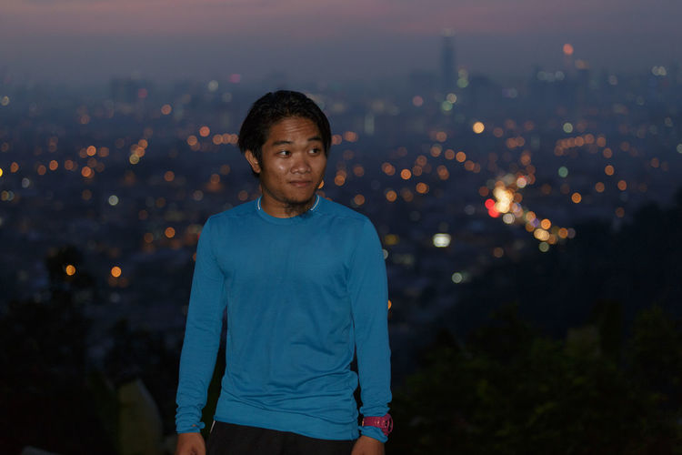 Man looking away while standing against illuminated city at dusk