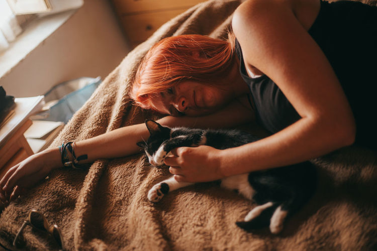 High angle view of woman lying on bed with cat at home