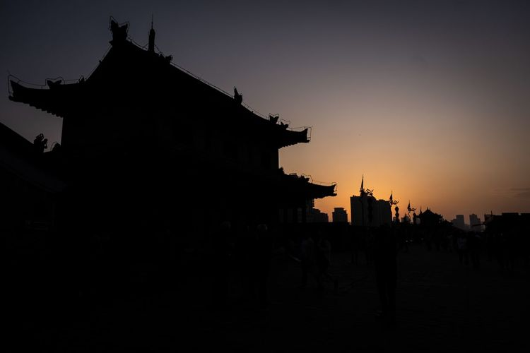 Silhouette buildings against clear sky at sunset
