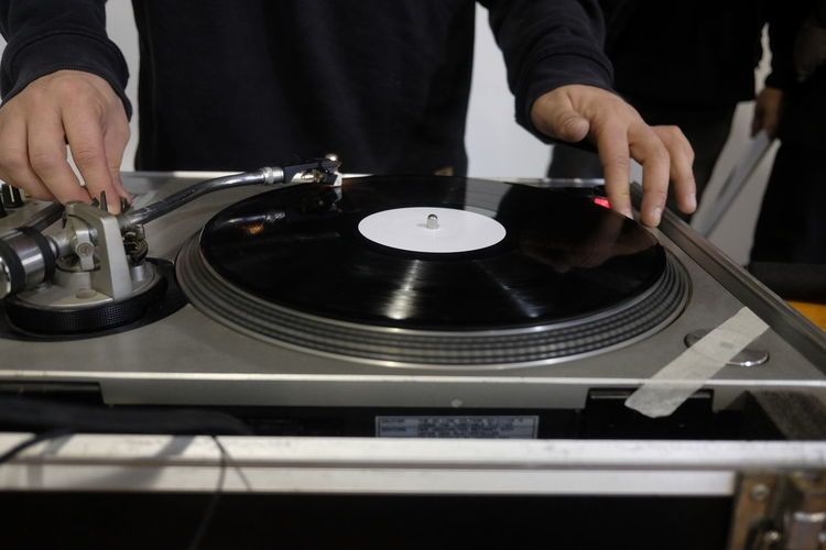 Midsection of man playing record