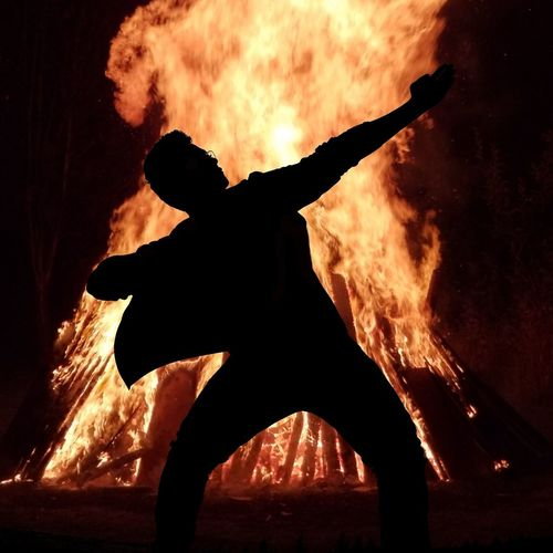 Low angle view of silhouette man against fire at night