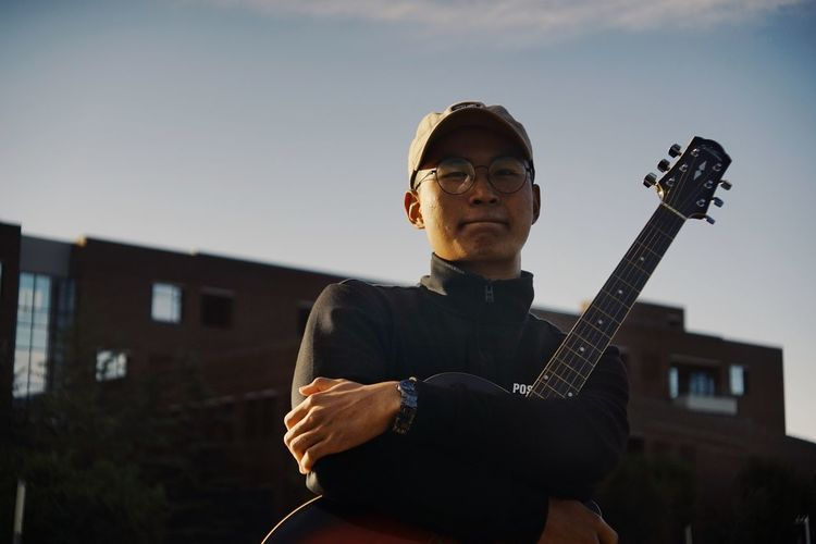 Acoustic Guitar Architecture Building Exterior Built Structure Casual Clothing Eyeglasses  Fashion Focus On Foreground Front View Glasses Guitar Music Musical Equipment Musical Instrument Musician One Person Outdoors Playing Plucking An Instrument Real People Skill  String Instrument Sunglasses Young Adult Young Men