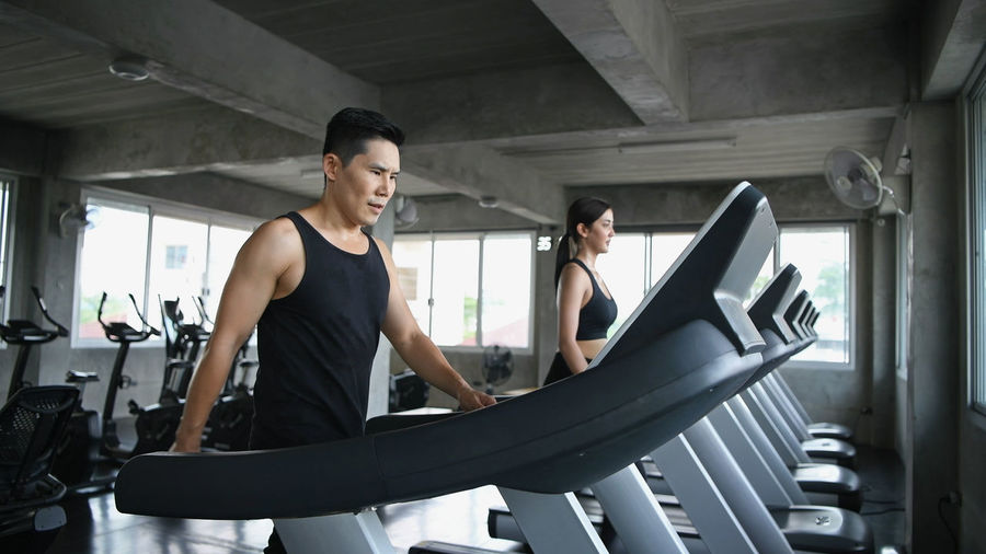 Exercise concept. Men and women are running together in the gym. Activities Asia Man Attentive Service Be Tired Beautiful Girl Beauty Women Body Builder Burn Calories Cardio Workout Caucasian Youth Cheerful Personality Coach Couple Asian Exercise Machine Family Day Fat Burning Fill Happiness Fitness Center Friends Request Friendship Forever Full Body Give Group Friend Gym Exercises Health Care Healthy Concept Holiday Vacation Husband And Wife Indoor Sport Japanese  Jogging Track Leg Strength Lifestyle Leisure Lose Weight Male Protection Equipment Run Way Runner Up Running Athlete Slim Fit Smile Together Sports Clothing Strong Muscle Sweat Gland Trainer Sneaker Training Course Two People Weight Loss Woman Young Adult
