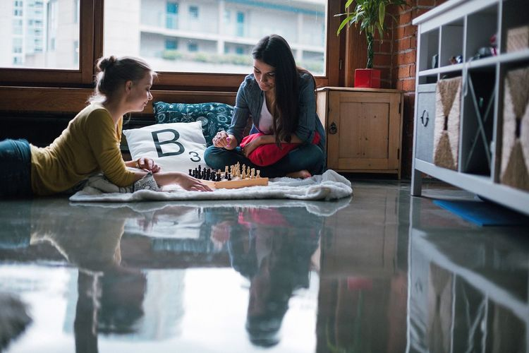 Women play chess on floor at home
