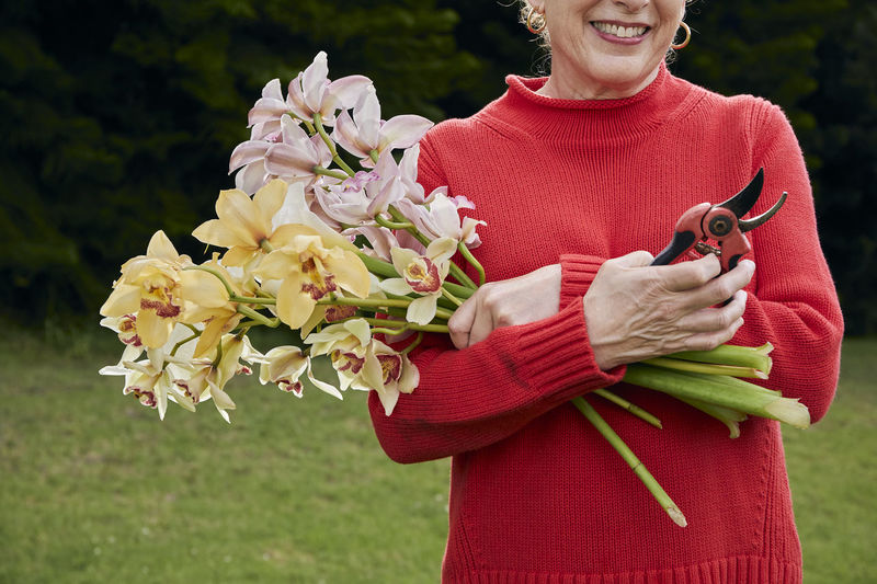 Low angle view of woman holding flower bouquet
