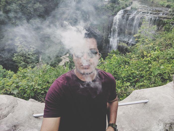 Man exhaling smoke against waterfall
