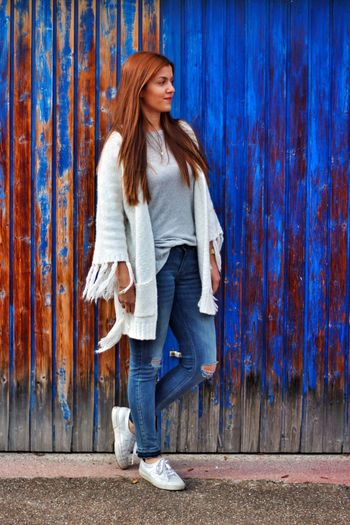 Full length of young woman looking away while standing against blue weathered wall