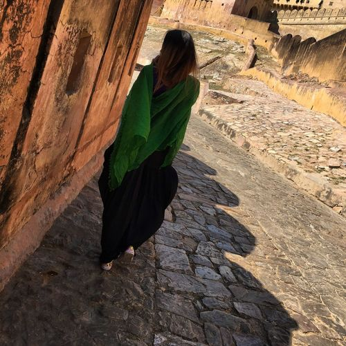 Rear View Of Woman Walking On Footpath By Fort During Sunny Day