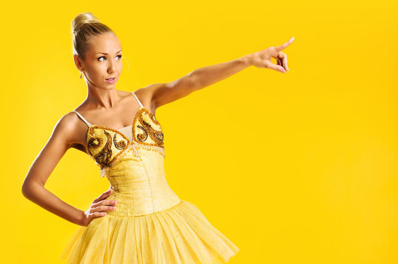 Beautiful ballerina pointing away against yellow background