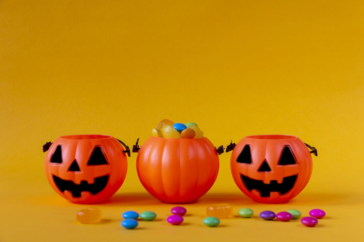 View of pumpkins against yellow background
