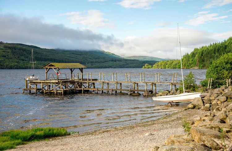 A small pebble beach and a wooden jetty in Loch Tay, central Scotland Boat Station Family Good Weather Hills Holiday Loch Tay Pier Scotland Tourist Attraction  Trees Calm Water Cloud Sky Forest Highlands Jetty Killin  Lake View Lakeshore Landscape Sailing Boat Summer Travel Destinations Vacation Wooden Yacht