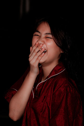 Beautiful young woman with eyes closed laughing while hands covering mouth