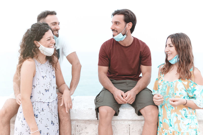 Smiling couple wearing flu mask talking while standing outdoors