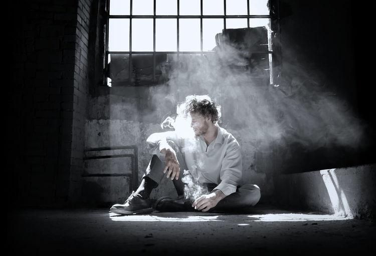 Man smoking while sitting on floor against window