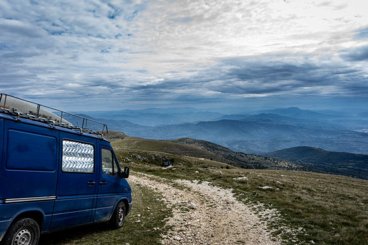 Car on road by mountains against sky