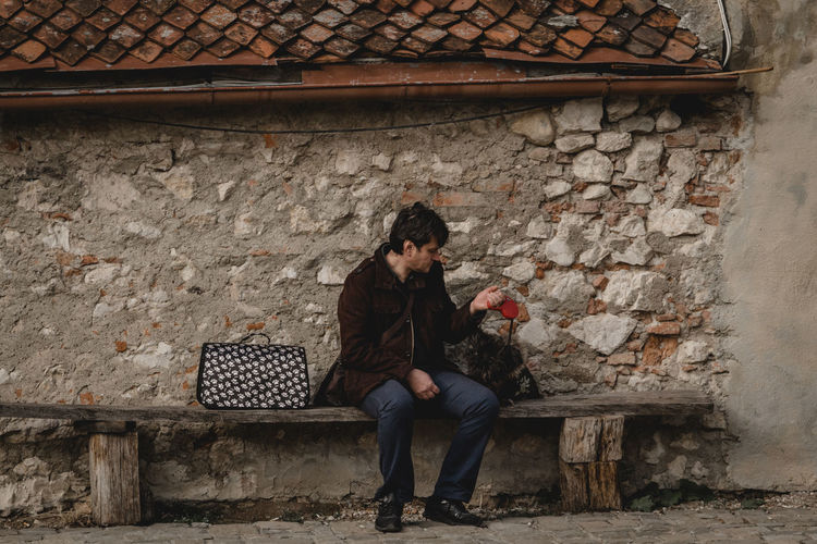 An owner of a dog sits with their pet on a bench against a stone wall in Rasnov Castle, Romania. - IG: @LostBoyMemoirs - IG: @LostBoyMemoirs Streetwise Photography Steetphotography Street Photography The Week on EyeEm Best EyeEm Shot My Best Photo Animal Themes Animals In Captivity People People Watching People Photography people and places Full Length One Person Wall - Building Feature Real People Architecture Built Structure Wall Lifestyles Young Adult Leisure Activity Front View Casual Clothing Adult Day Sitting Looking Clothing Women Young Women Stone Wall Brick Outdoors Scarf Leather Warm Clothing The Art Of Street Photography