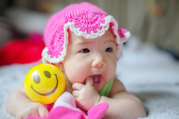 Cute baby girl with toy on bed