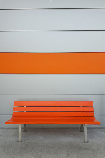 Empty orange bench by wall