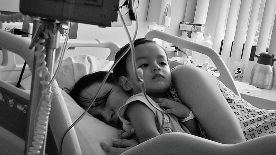 Mother With Son On Bed In Hospital