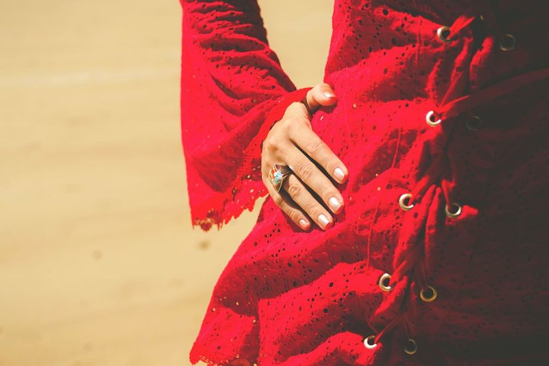 Midsection of woman in red dress with hand on hip