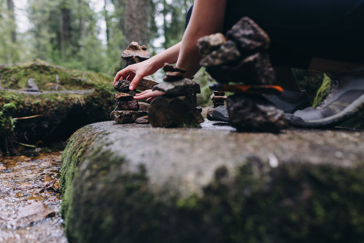 Midsection of woman sitting on rock in forest stacking stones