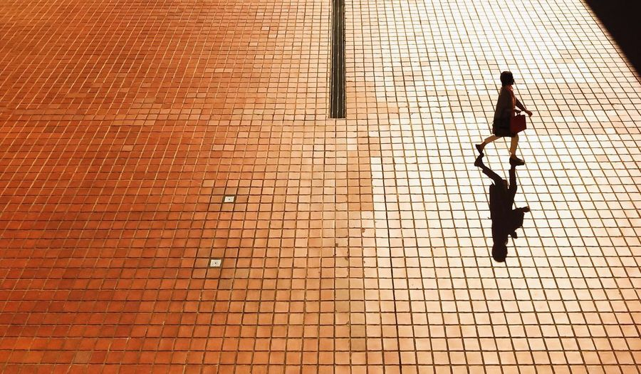 High angle view of woman walking on tiled ground