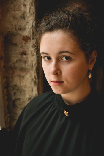 Close-up portrait of young woman standing against wall