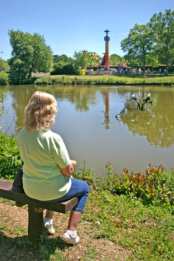 Woman sitting on a bench looking over the look at a theme park in the UK. Lady Woman Amusement Park Amusement Park Ride Casual Clothing Childhood Day Female Full Length Hair Hairstyle Lake Leisure Activity Lifestyles Nature One Person Outdoors Plant Real People Rear View Sitting Sunlight Tree Water Women