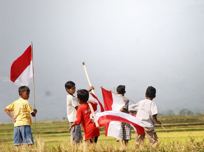 Boys holding flags while standing on grassy field against sky