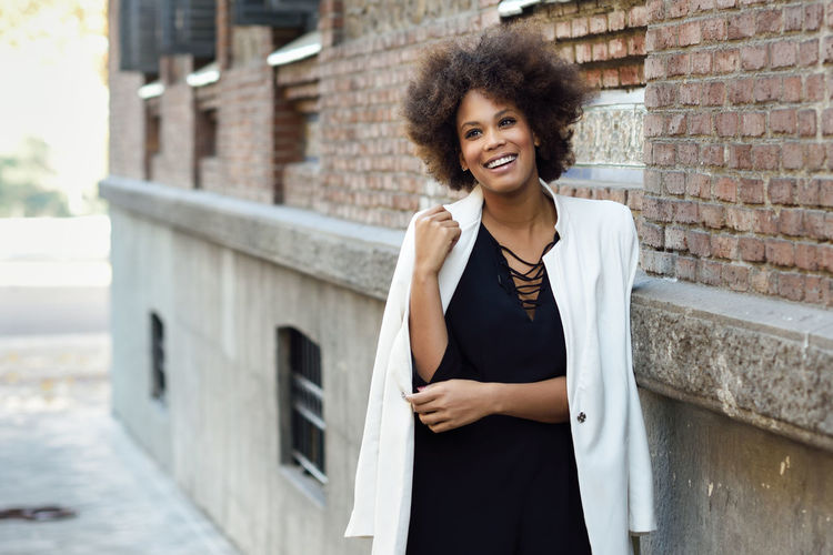 Young black woman with afro hairstyle standing in urban background. Mixed girl wearing white jacket and black dress posing near a brick wall Architecture Beautiful Woman Beauty Brick Building Exterior Built Structure Emotion Focus On Foreground Front View Hair Hairstyle Happiness Looking At Camera One Person Portrait Real People Smiling Standing Wall Wall - Building Feature Women Young Adult Young Women