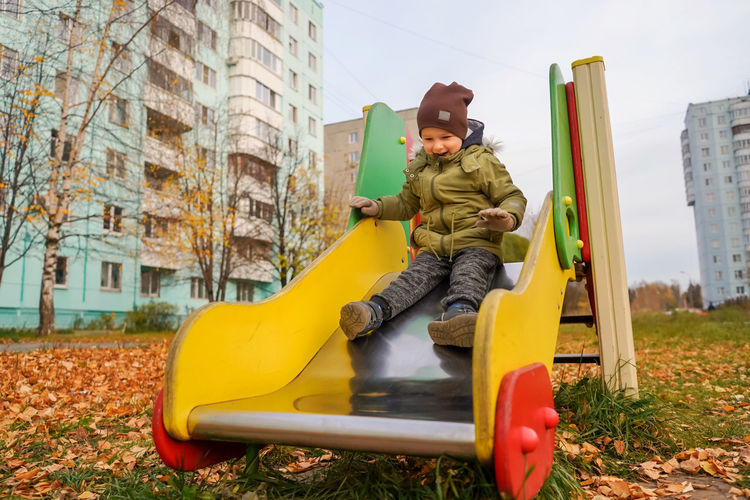 Full length of boy sitting on slide at playground