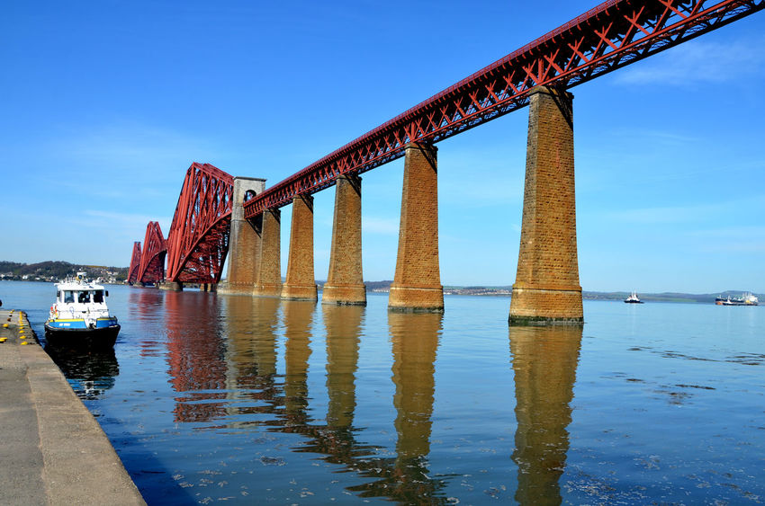 Architecture Built Structure Engineering Forth Bridge Forth Of Firth No People Outdoors Red Bridge Reflection Rippled River Scotland Sky Steel Steel Structure  Stone Tower Sunny Day Tourism Train Bridge Travel Destinations Victorian Architecture Water