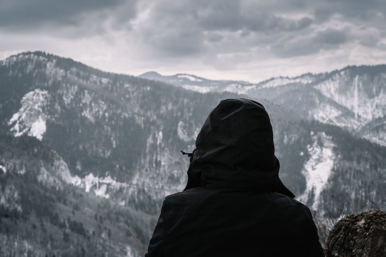 Rear view of person in black winter jacket looking at snowcapped mountains in winter