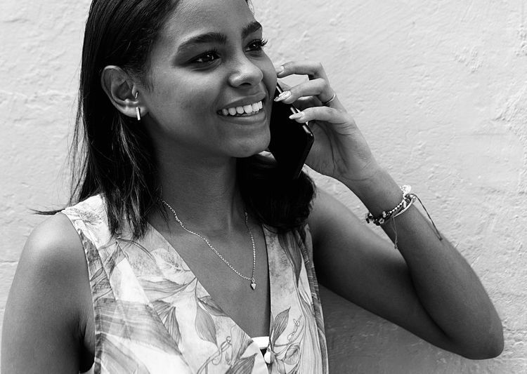 Portrait of smiling young woman using mobile phone against wall