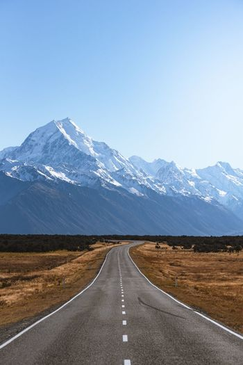 Empty road leading towards snowcapped mountains against sky