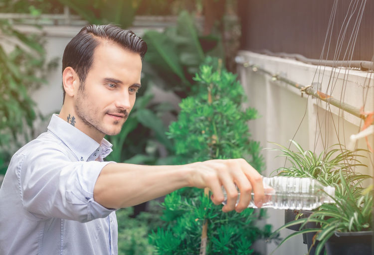 Young Man Watering Plant In Back Yard