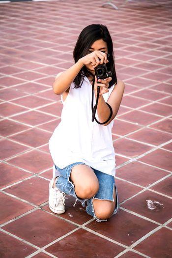 Portrait of teenage girl photographing