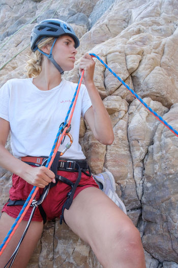 Woman holding ropes while standing against rock