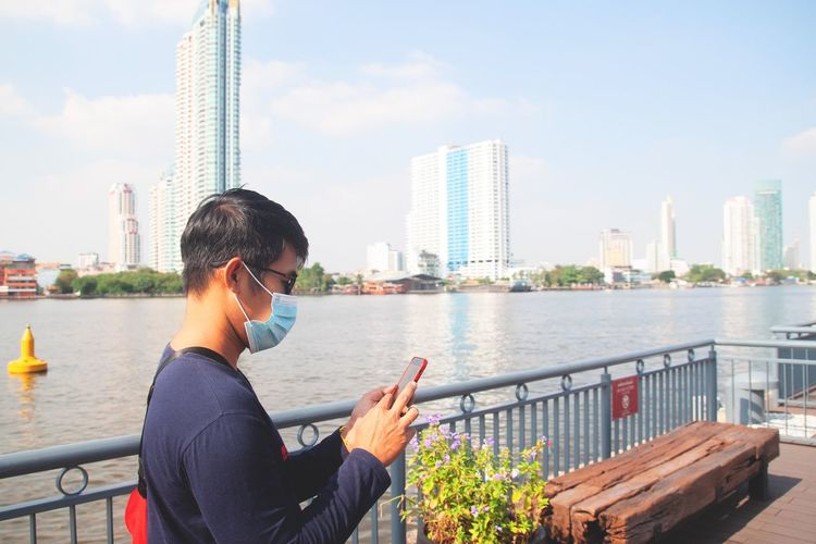 Man using smart phone by river in city against sky