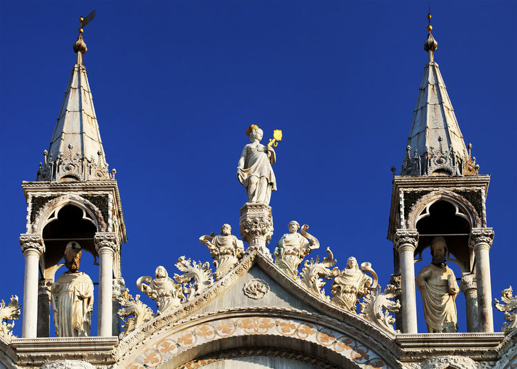 Statues and carvings on saint mark basilica against clear blue sky