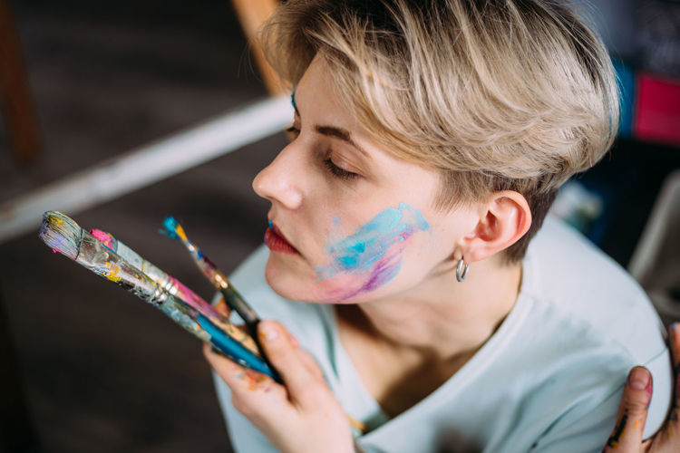 Creative portrait of beautiful young woman artist in studio with brushes.