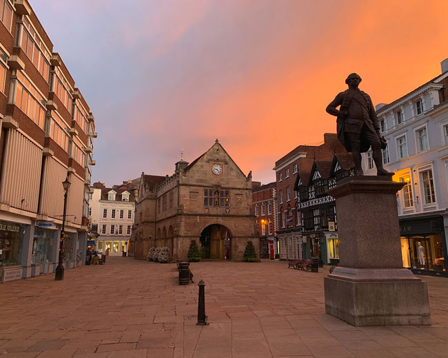 Statue on street amidst buildings against sky at sunset