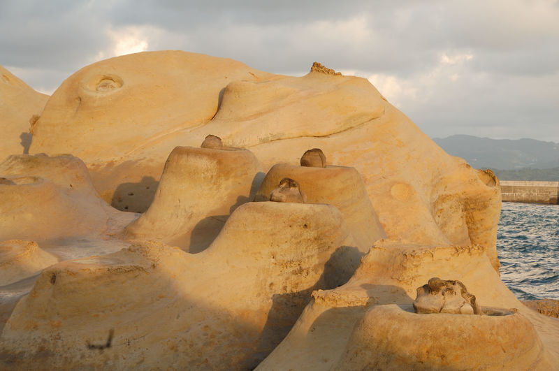 View of rock formations against cloudy sky