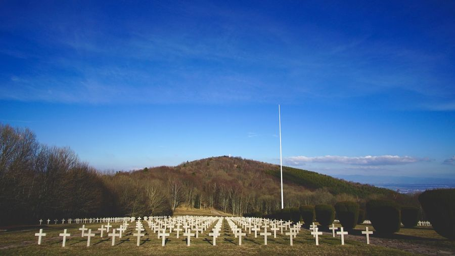 Scenic view of cemetery against blue sky