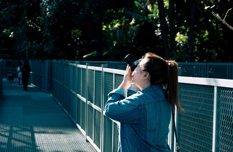 Woman photographing on footbridge
