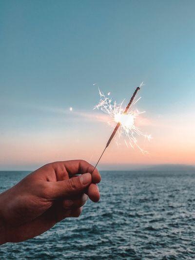 Cropped hand holding lit sparkler against sea