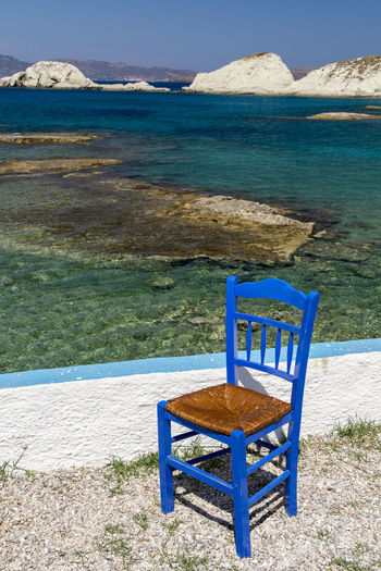 Single blue painted chair by the sea with a view of the Cyclades in the background Chair Cyclades Islands Greece Photos Greek Islands Mediterranean  Painted Terrace Vacations Blue Cafe Chairs Chairs And A Table Closed Culture Culture And Tradition Day Greece Ios No People Old Outside Scenics Taverna Traditional Tranquil Scene