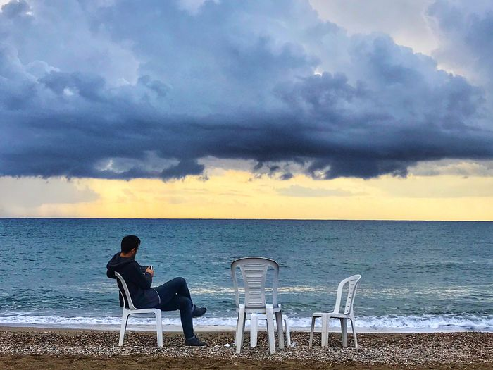 Sea and men Water Sky Cloud - Sky Sea Horizon Over Water Horizon Beach Nature Sitting Land Beauty In Nature Leisure Activity Scenics - Nature Chair Real People Seat Adult Men People Outdoors