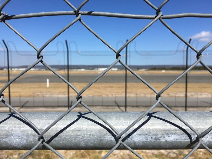 Close-up of chainlink fence against airport runway